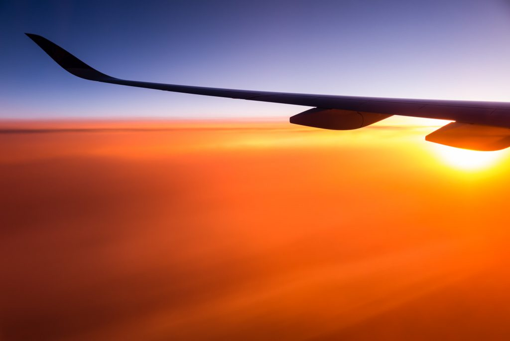An aeroplane wing at sunset